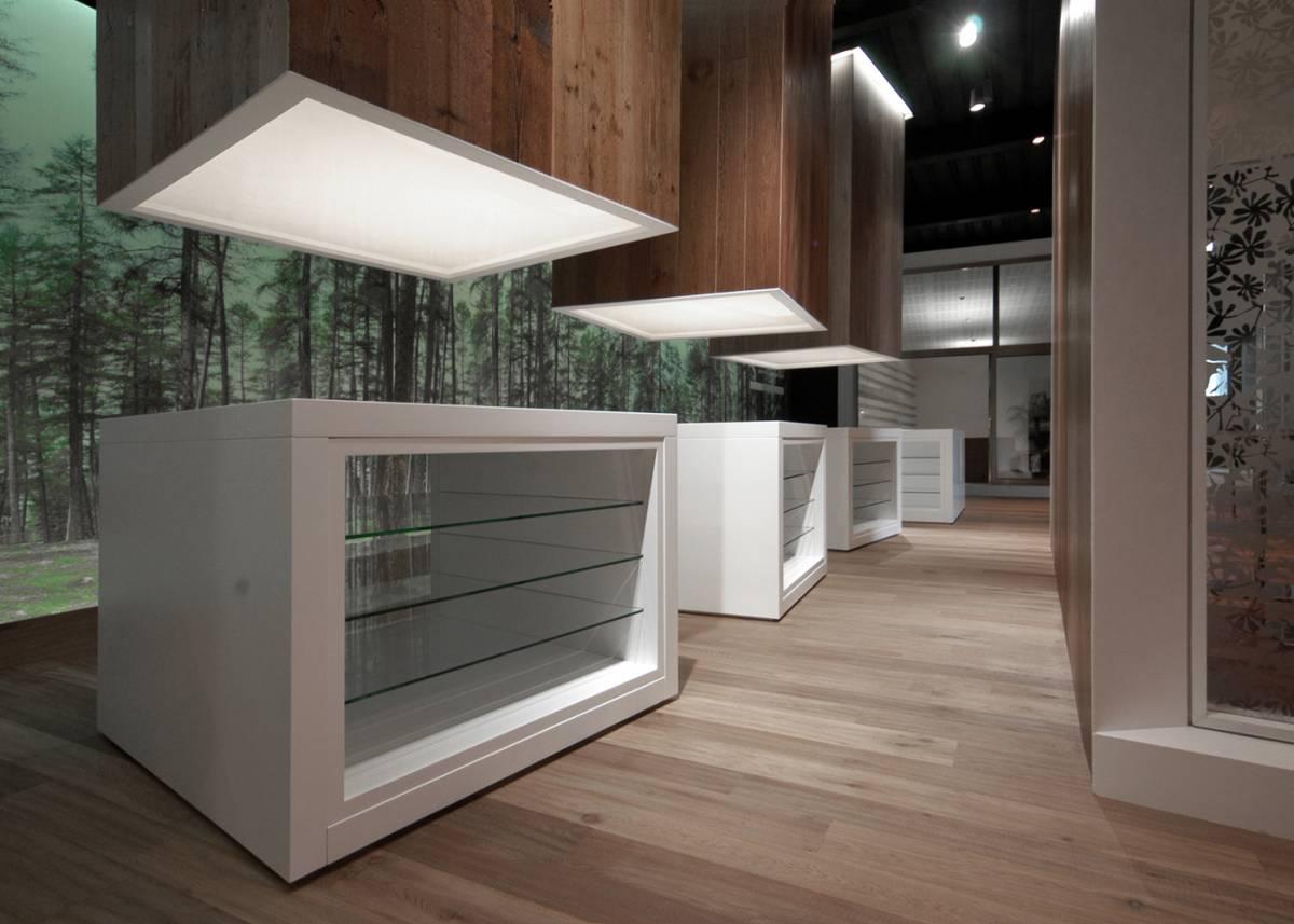 contenitori espositivi e facciata retroilluminata con immagine del bosco