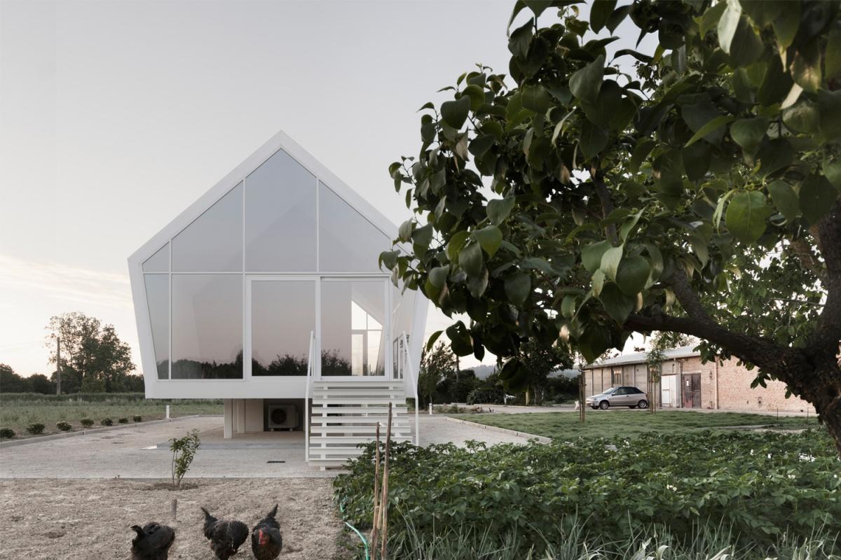 facciata di casa nell'orto carciofi e galline