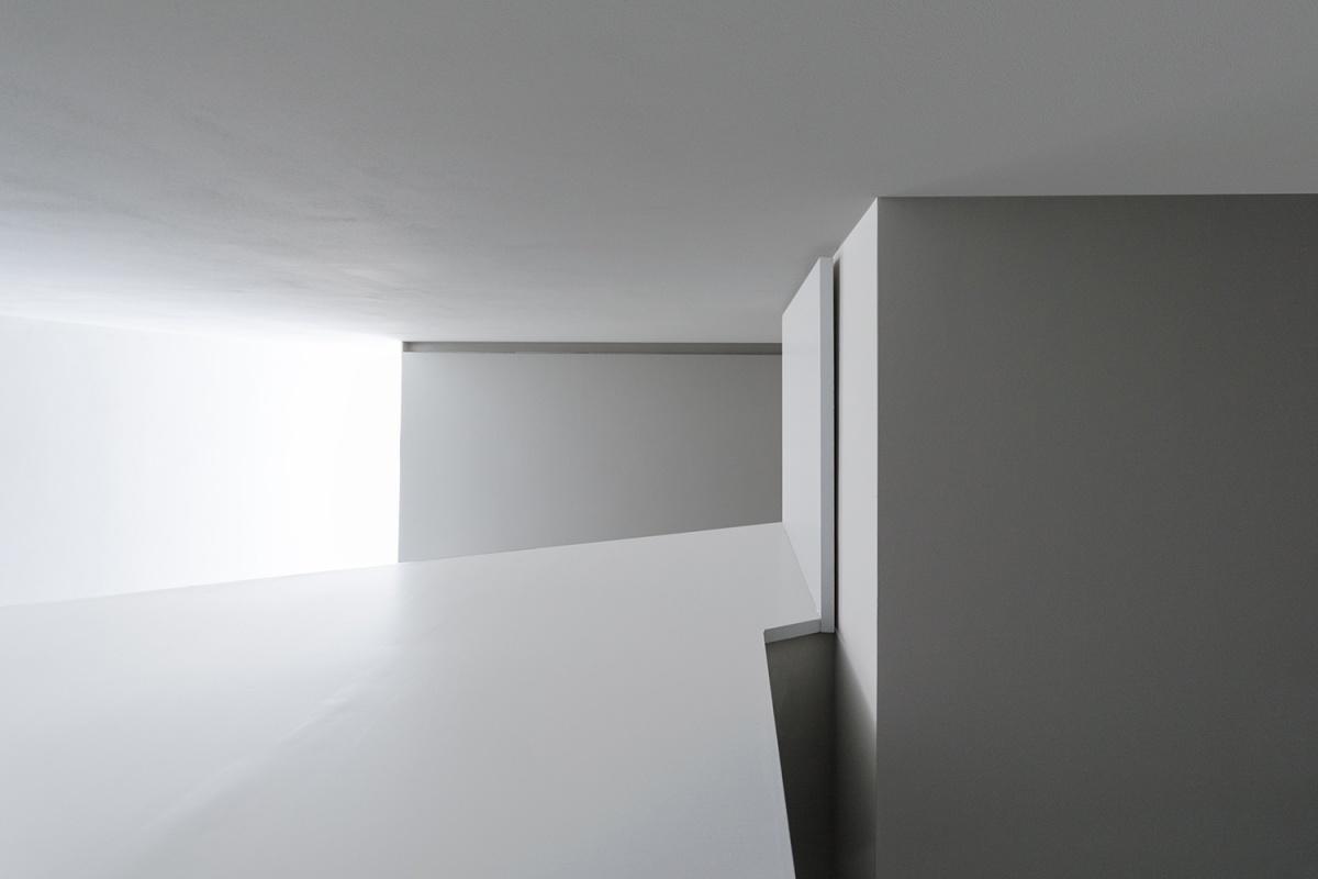 scala antincendio architettura contemporanea minimale di casa verde rapporto con la luce naturale discendente dall'alto dal lucernario