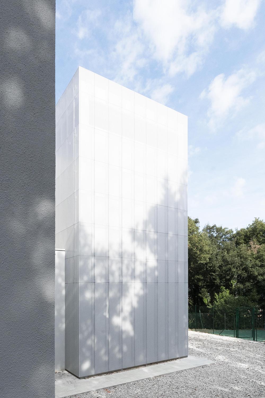 immagine della scala antincendio di casa verde rivestita in lamiera forata bianca ben integrata nel bosco di lecci