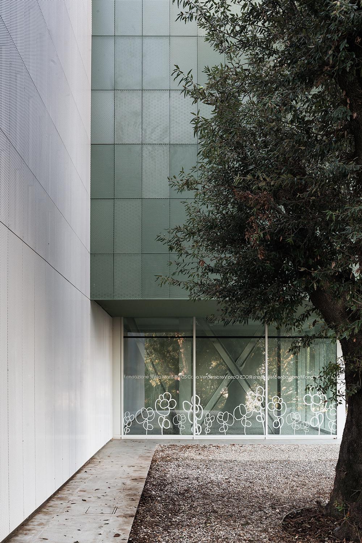 casa verde nel rapporto tra architettura paesaggio e bosco e la facciata minimale in metallo