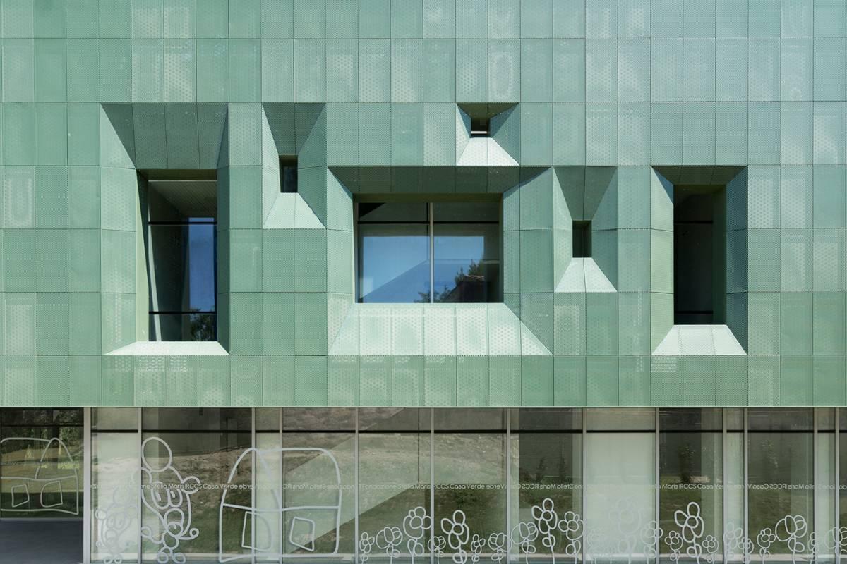 immagine di una facciata in vetro e lamiera microforata verde ventilata per il risparmio energetico