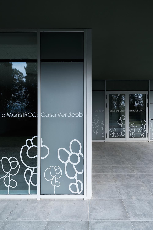 disegni adesivi sulla facciata continua di ingresso alla clinica casa verde