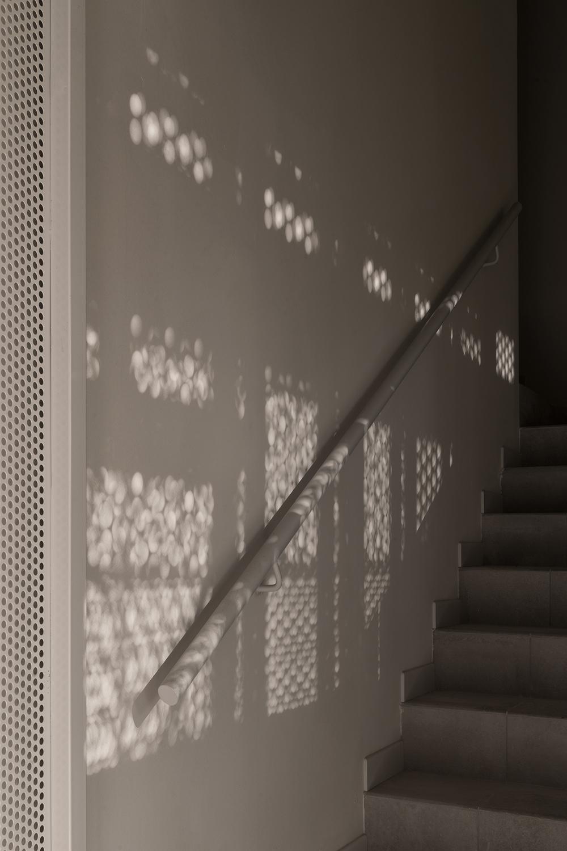 progetto interni monocromatico minimalista con giochi di luce su vano scala contemporaneo